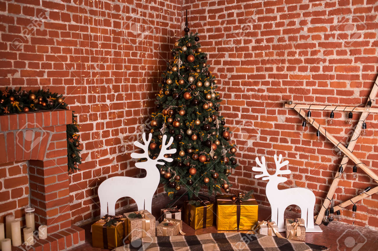 Decorated Christmas tree with orange balls, golden gifts and white deers. Warm colors. Studio horizontal colorful photo - 64057235