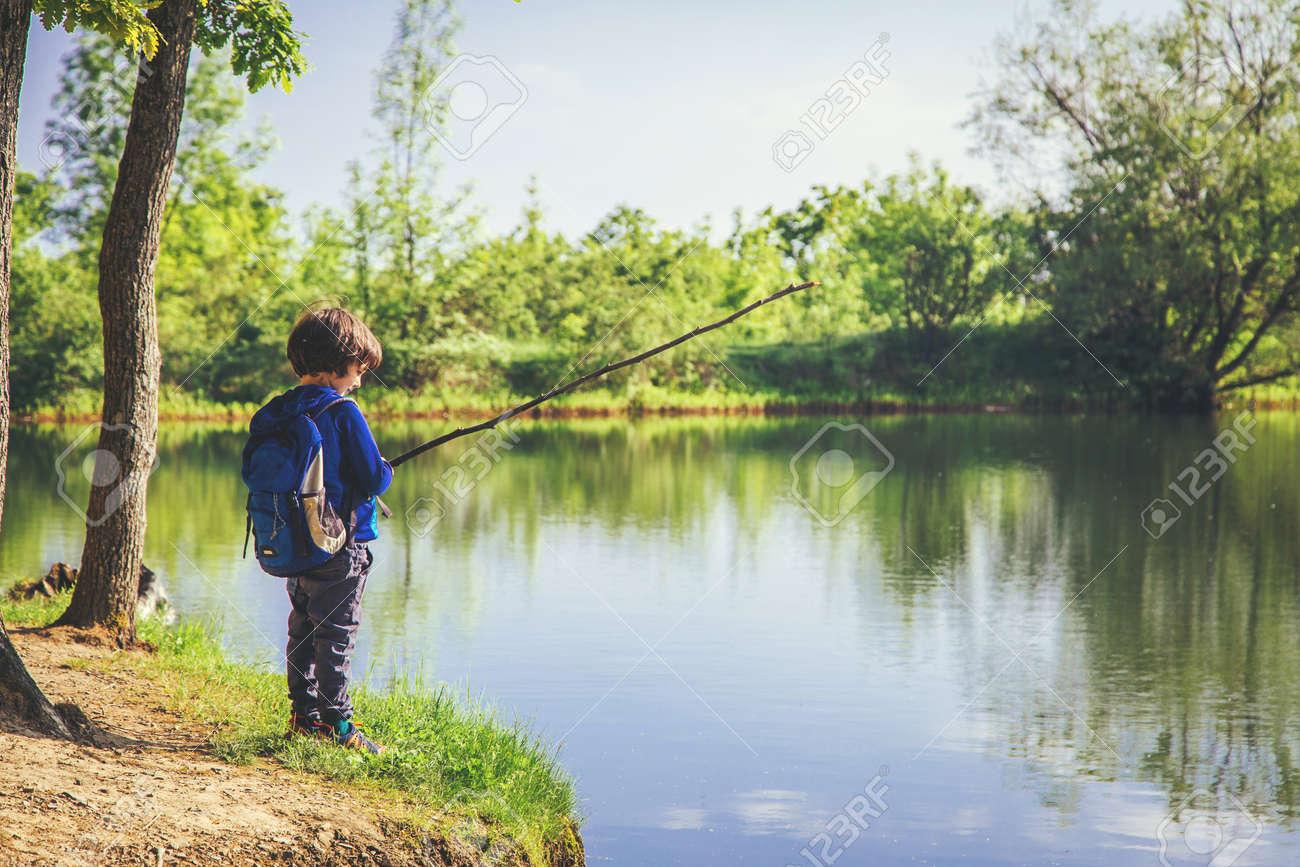 Little kid play with stick looks like rod and fishing on the lake in the forest on a sunny day. - 125795376