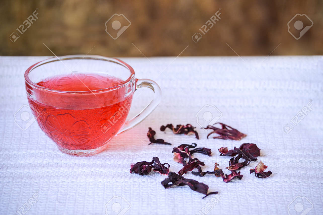 Cup of hibiscus tea in transparent cup on white tablecloth beside cup of hibiscus tea in transparent cup on white tablecloth beside dried hibiscus flowers stock photo izmirmasajfo