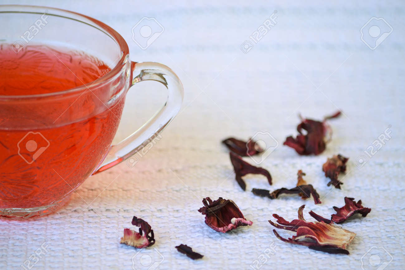 Closeup Of Of Hibiscus Tea In Transparent Cup On White Tablecloth