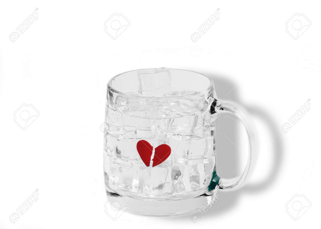 A Broken Red Heart Frozen Inside A Transparent Cup Filled With Ice Cubes  And Water,