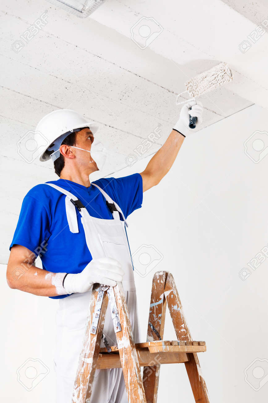 Painter With Helmet Gloves And Mask Painting Ceiling With Paint