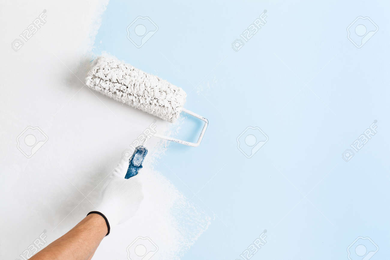 Close up of painter hand in white glove painting a wall with paint roller; copy space - 52884259