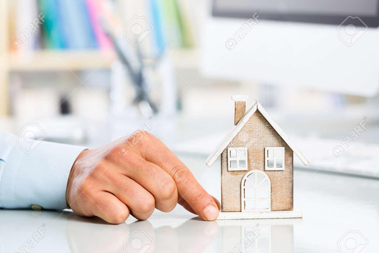 Homme à la main et de la chambre miniature dans pc de bureau