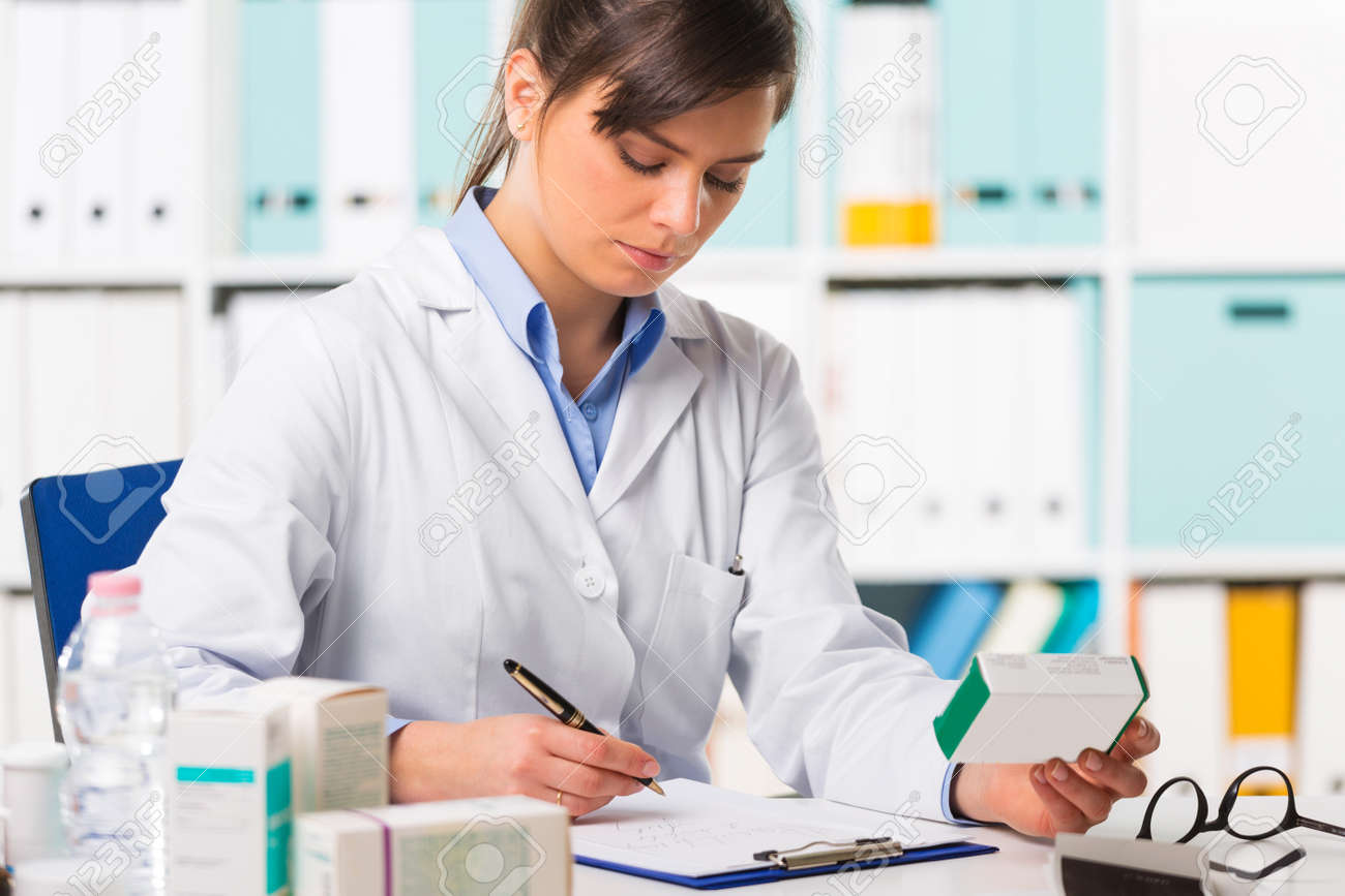 Pretty Young Female Pharmacist In White Coat Sat At Desk Writing ...
