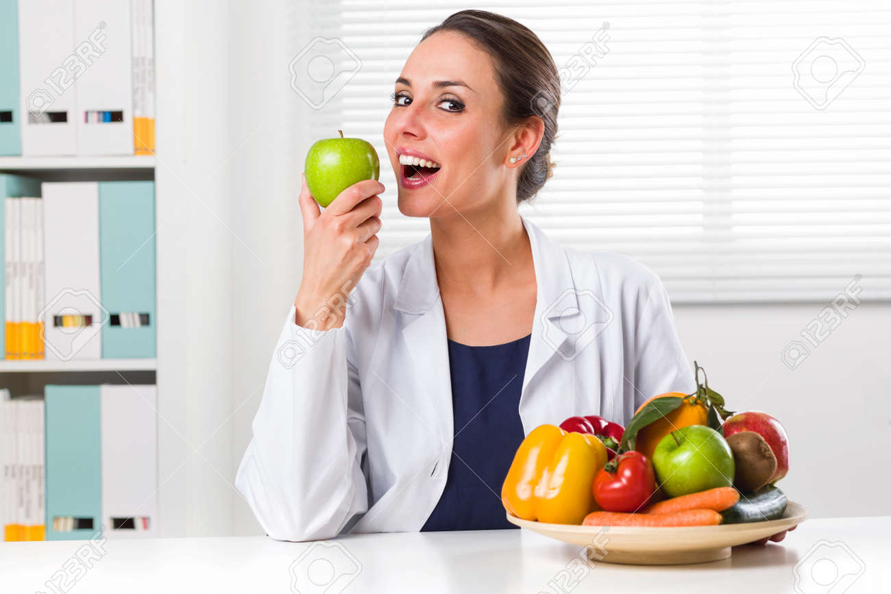 smiling female nutritionist eating a green apple in her office and showing healthy vegetables and fruits
