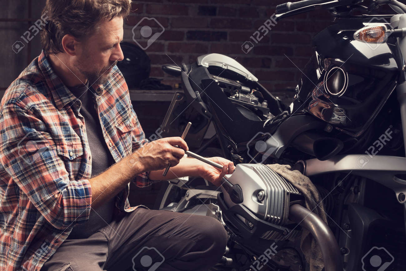 Mechanic using a plug spanner on a vintage motorcycle in a closeup as he does repairs or maintenance in a workshop - 134300159