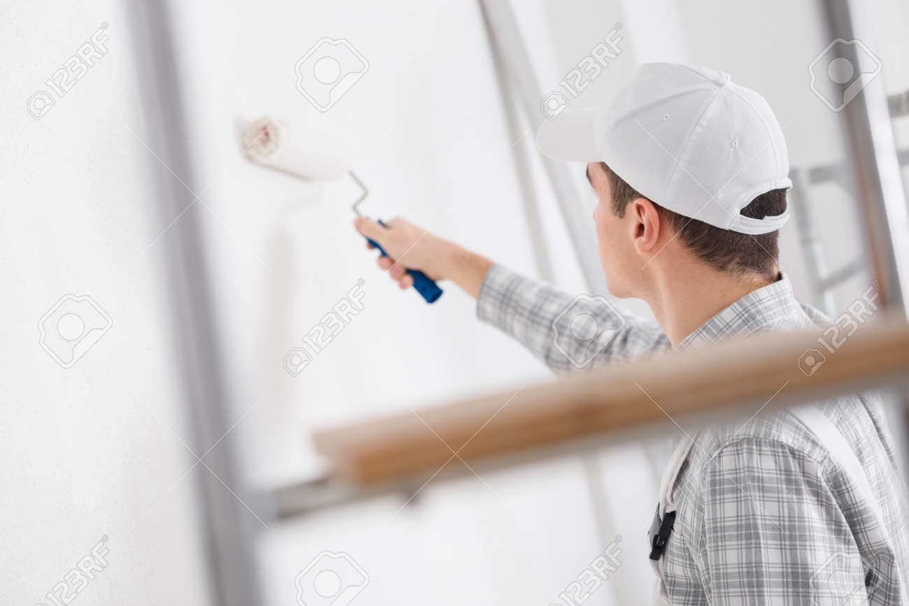 Young painter painting a white wall with a roller during renovations or construction viewed through a ladder - 144861452