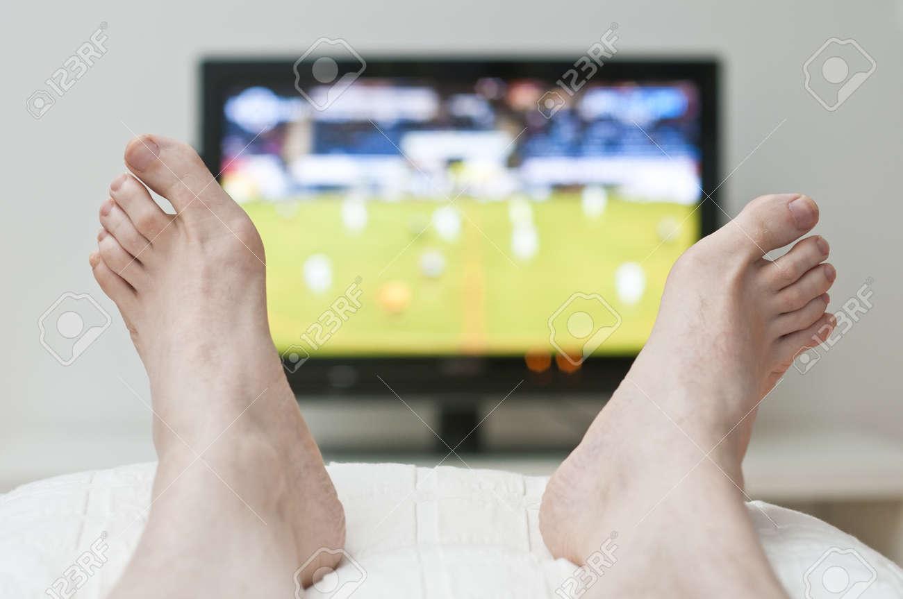 Tele Au Pied Du Lit tv allongé sur le lit et regarder entre les pieds nus