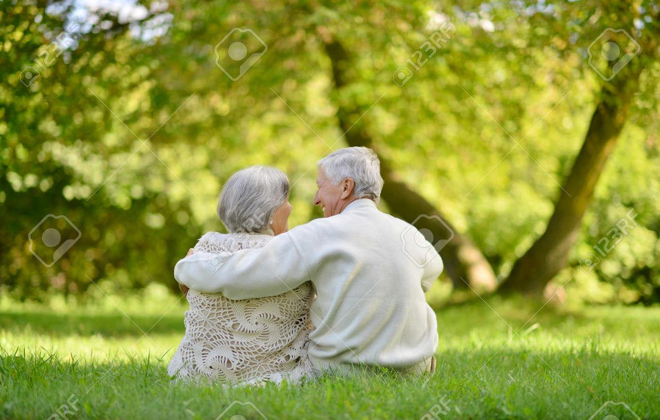 Happy elderly couple sitting in autumn park - 47390480
