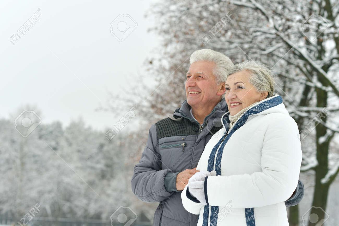 Portrait of elderly couple having fun outdoors in winter forest - 47639616