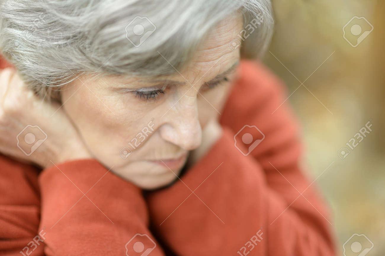 Nice sad old woman on the autumn background - 47928454