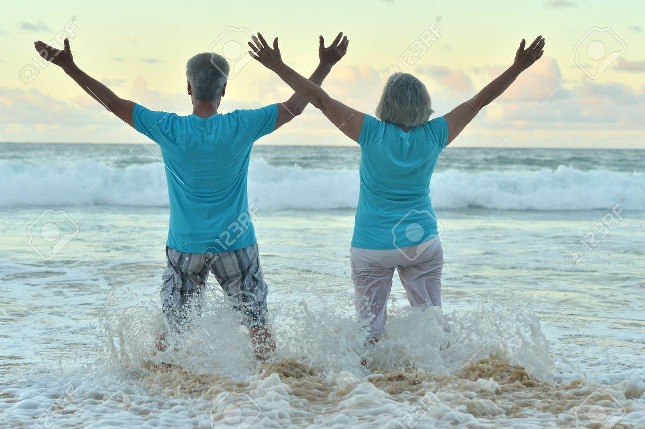 Beautiful happy elderly couple rest at tropical resort with hands up - 50745770