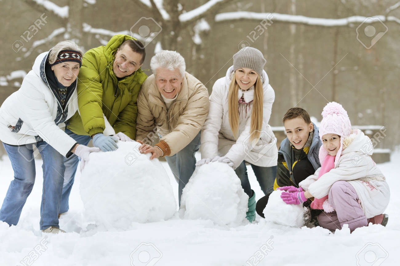 happy young family playing in fresh snow and building snowman at beautiful sunny winter day outdoor in nature - 52486825