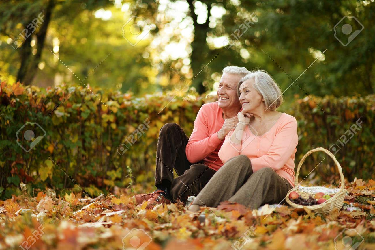 Beautiful caucasian elderly couple in the park in autumn - 52625014