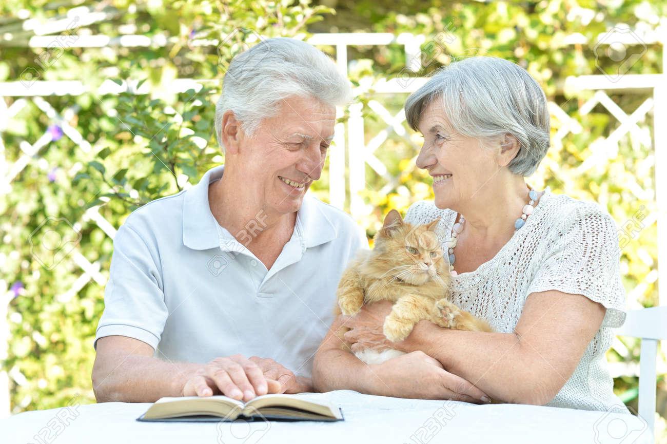 Happy senior couple on the veranda with cat - 53745869