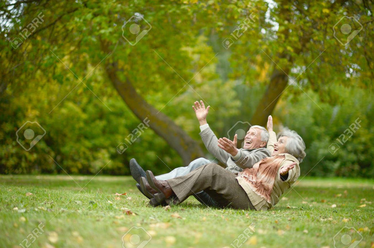 Beautiful caucasian elderly couple in the park in autumn - 54099302
