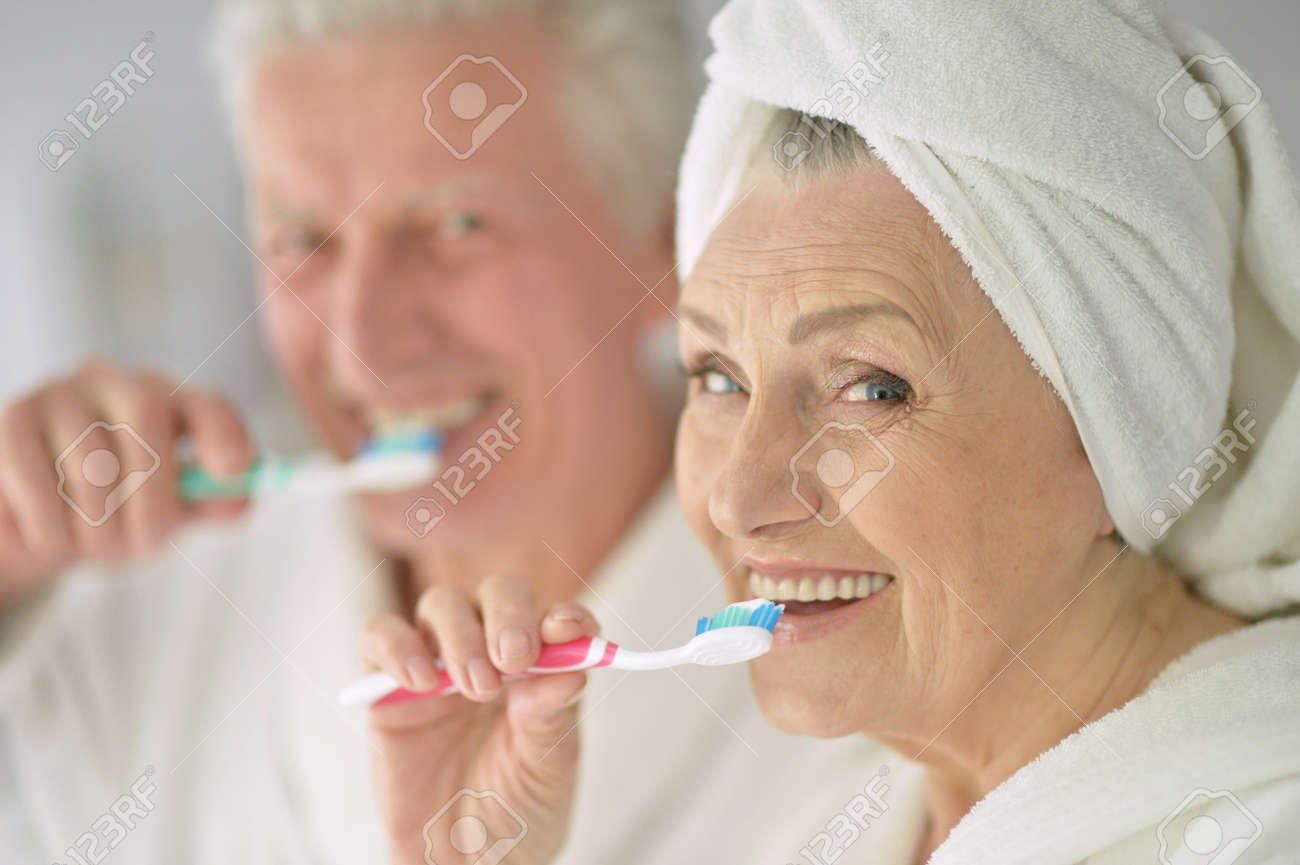 Senior couple with toobrushes in a bath - 57830904