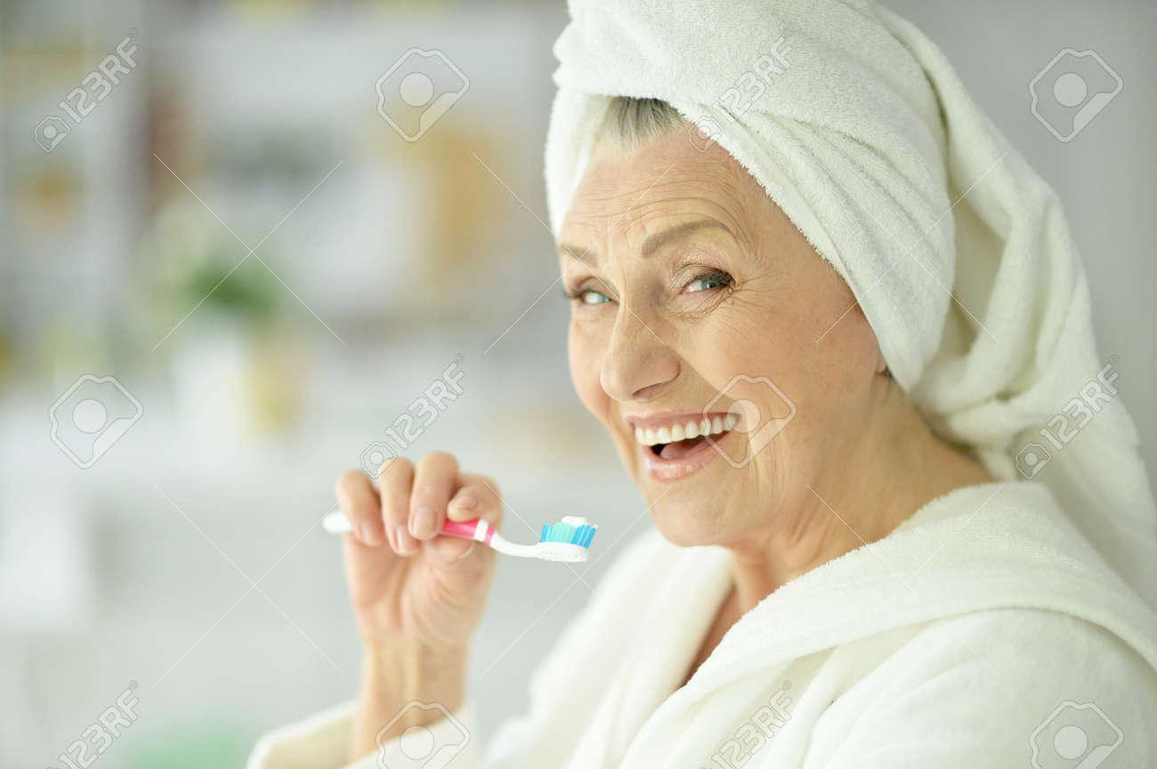 elderly woman brushing her teeth in the bathroom - 58680466