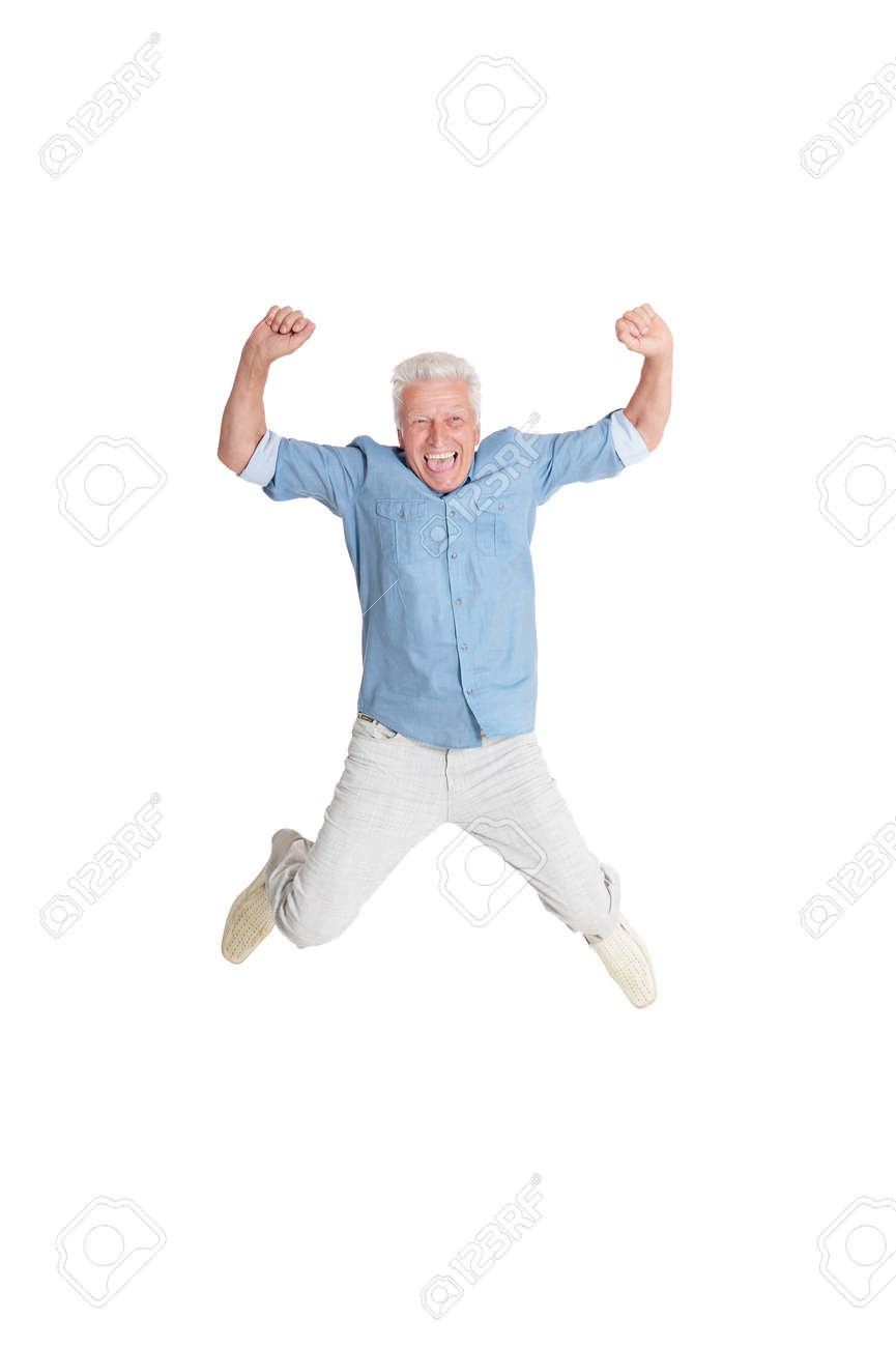 happy senior man in shirt jumping with hands up on white background - 60316956