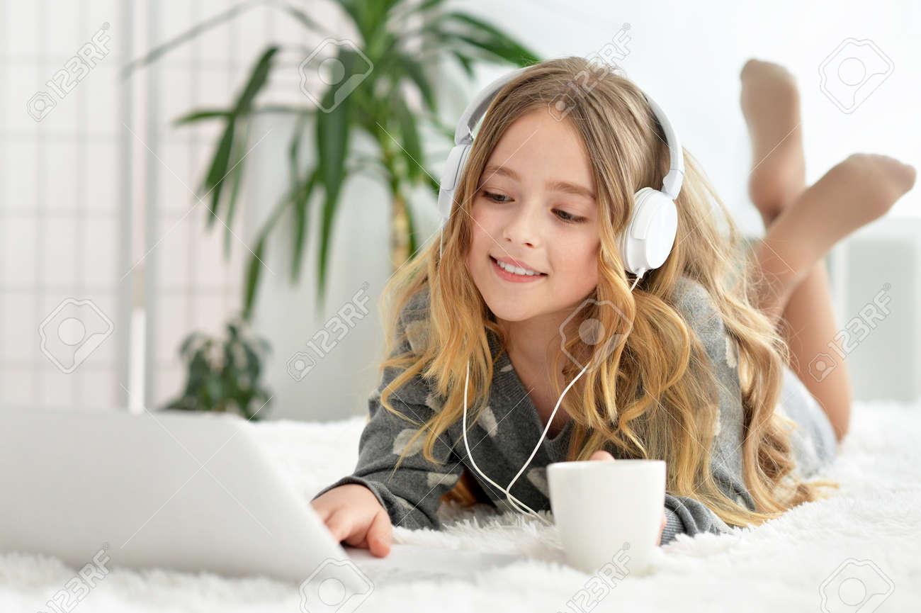 Portrait of a little cute blonde girl using computer - 61300357