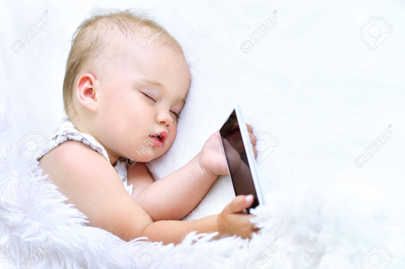 5e2508de25b5 Cute Sleeping Baby Girl With Smartphone In Bed Stock Photo