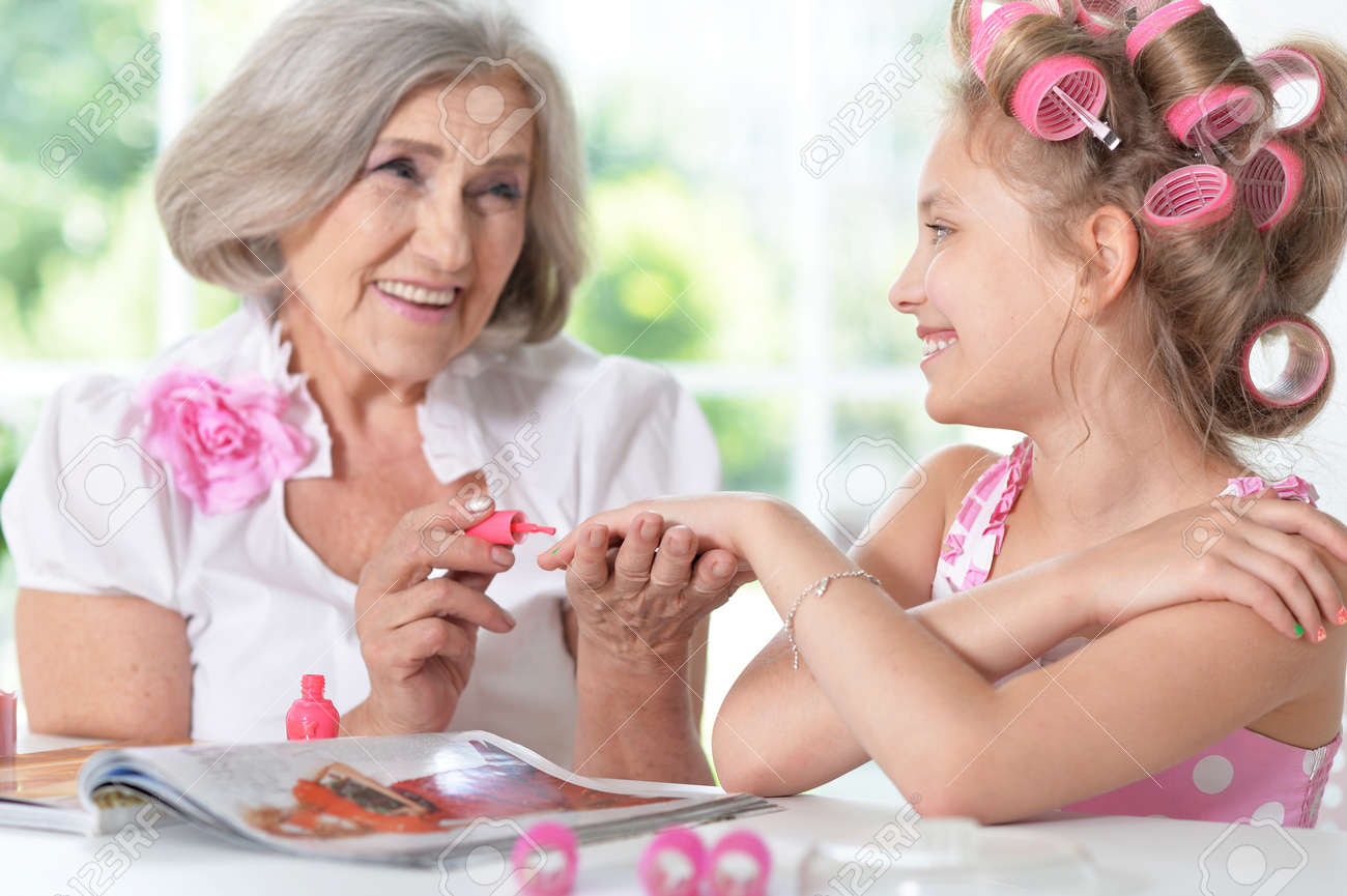 Cute Little Girl In Hair Curlers With Granny With Magazine.. Stock ...