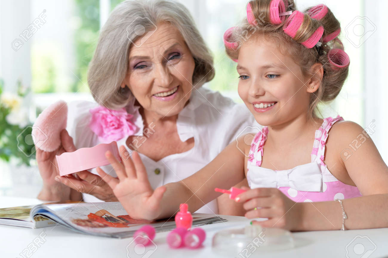 Cute little girl in hair curlers with granny with magazine..
