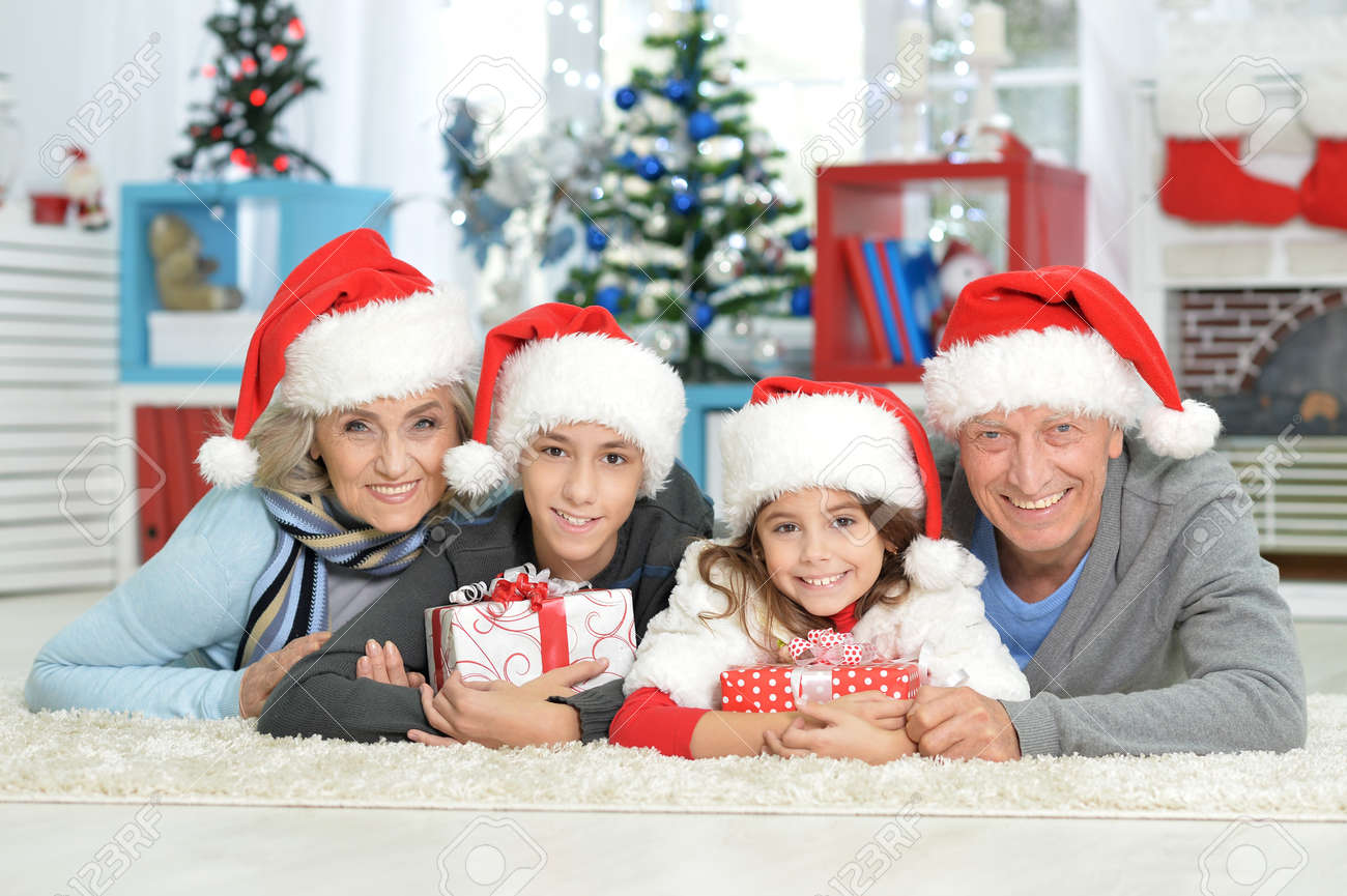Happy Grandparents With Grandchildren Celebrating Christmas Lying ...