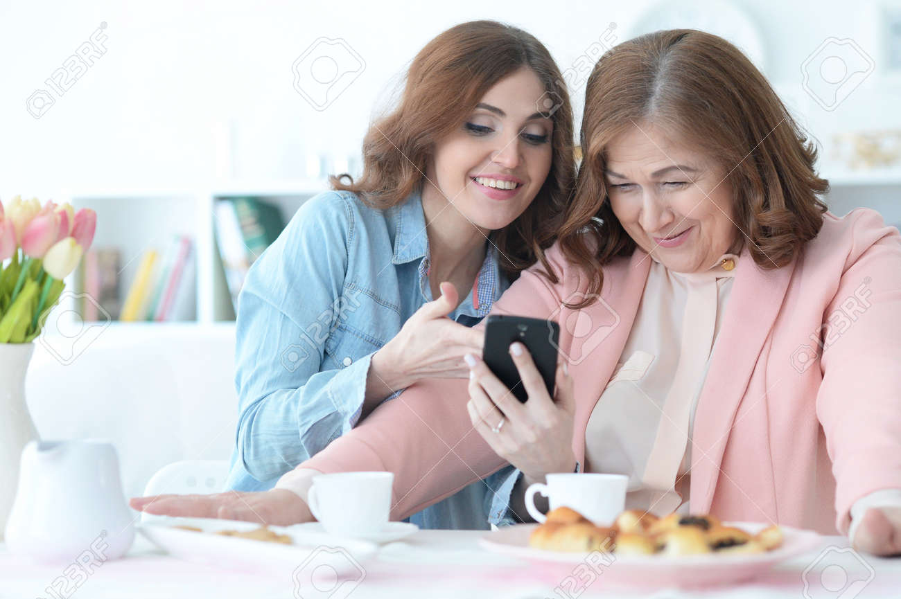 Daughter teaches an elderly mother to use a mobile phone - 77347293