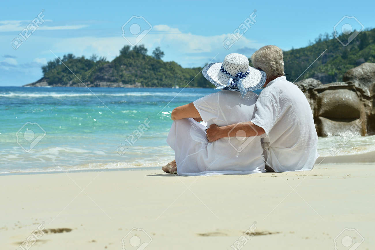 Portrait of a senior couple resting on beach - 80914793