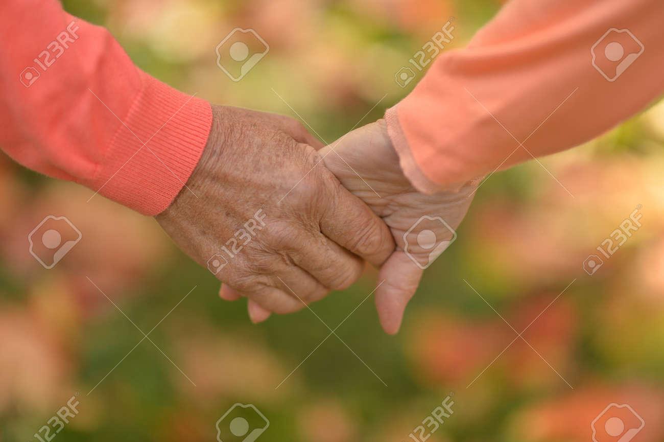 Pareja De Ancianos Tomados De La Mano En El Parque De Otoño Fotos