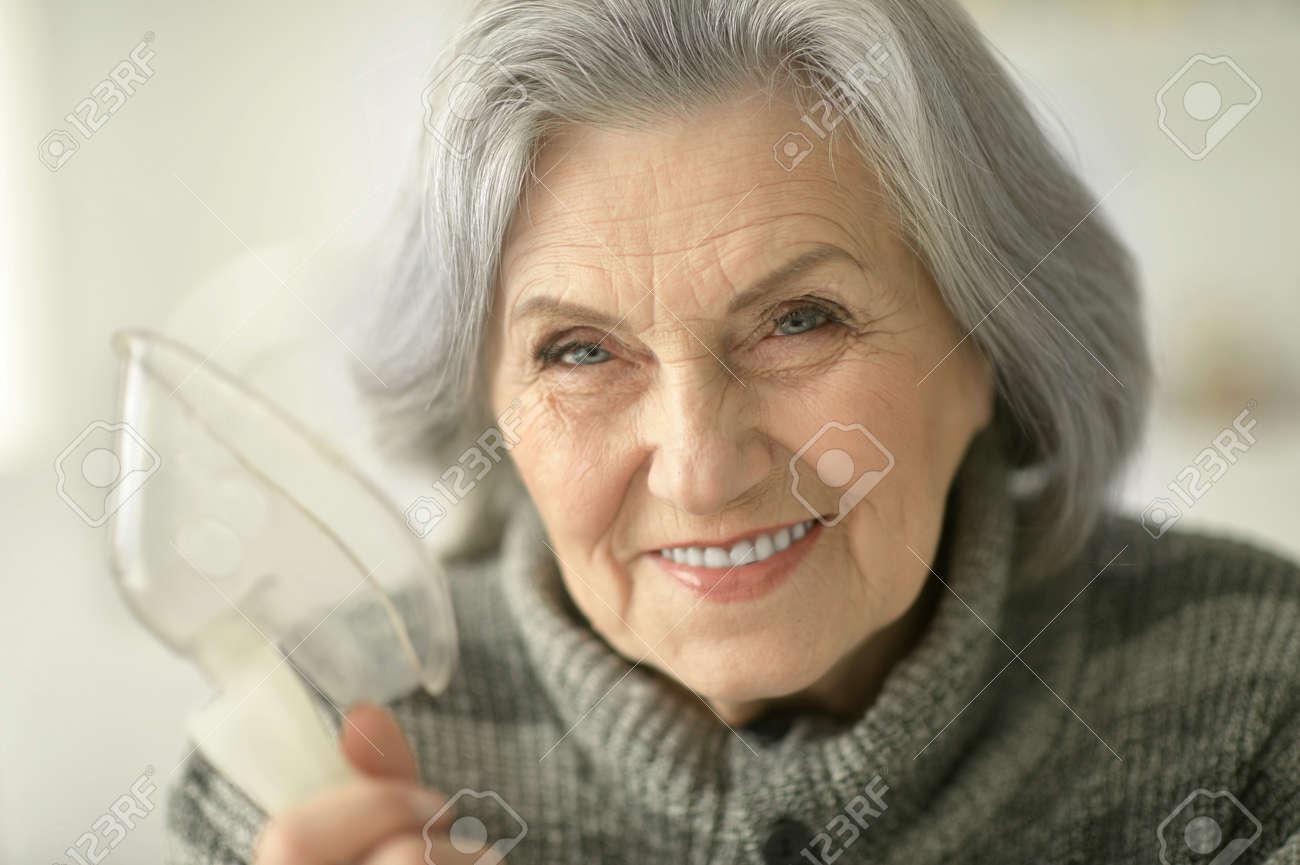 Senior woman making inhalation - 92015481