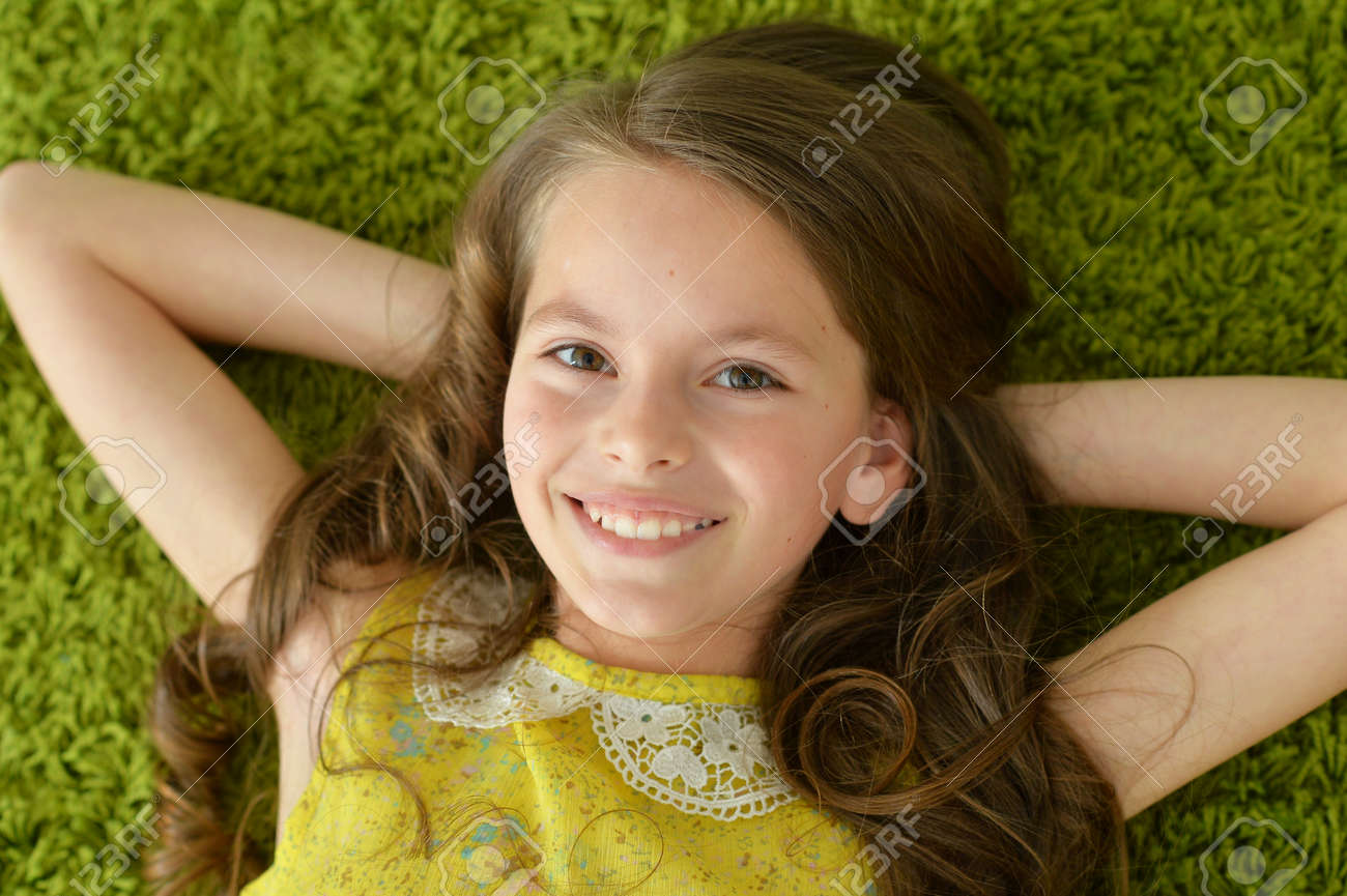 Close-up portrait of funny smiling little girl lying on green carpet - 114614564