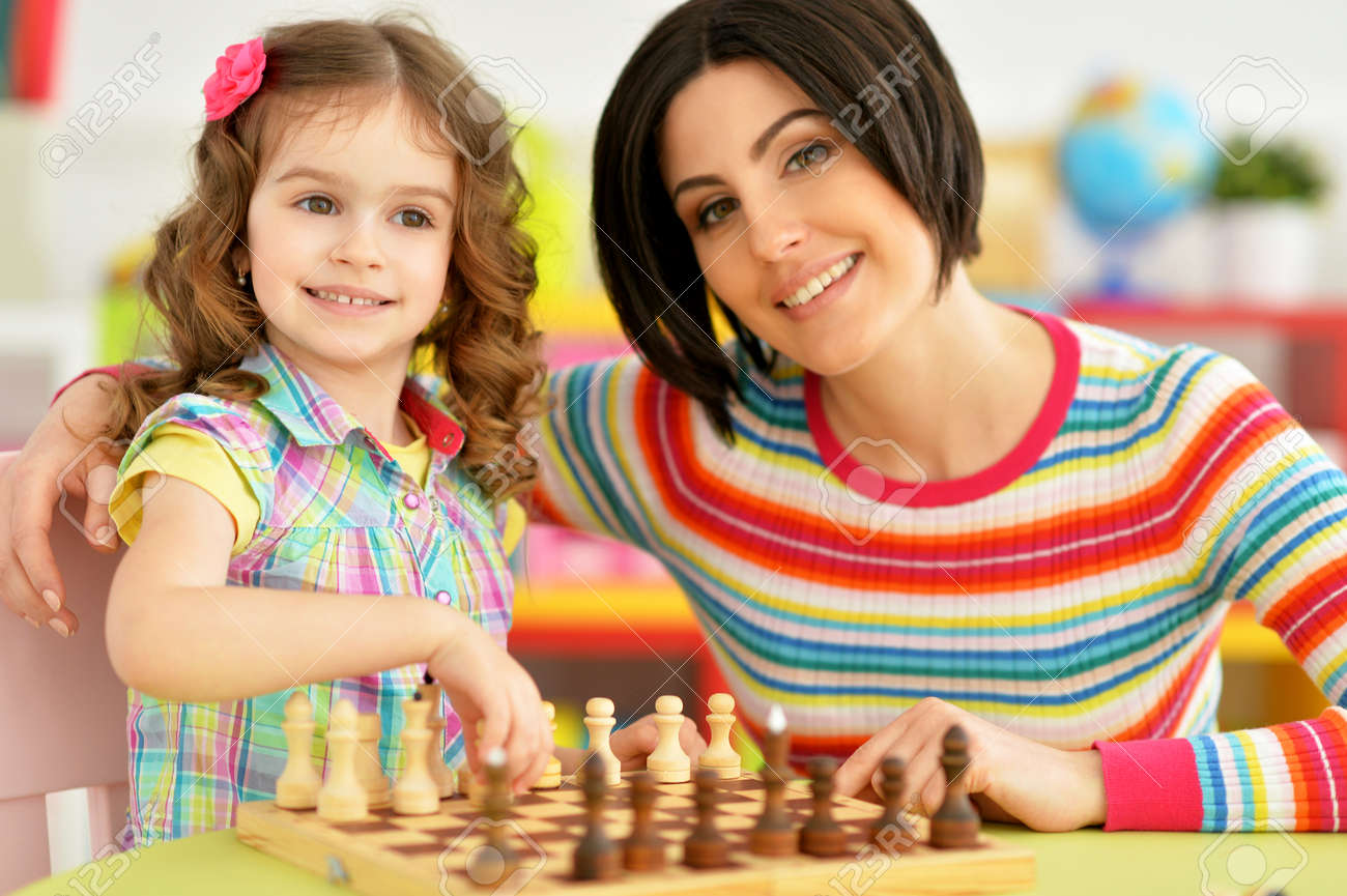 Portrait of beautiful young mother with her cute little daughter playing chess - 128858770