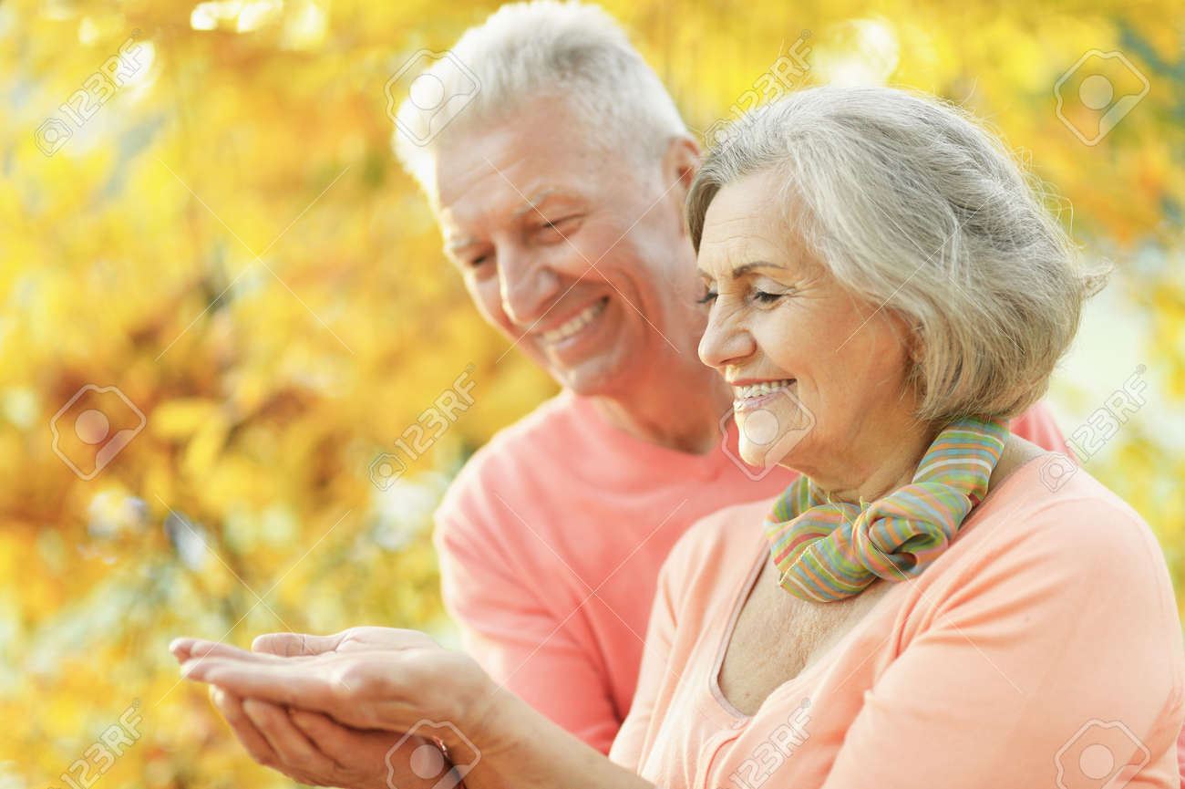 Senior couple in the park showing something - 139291481