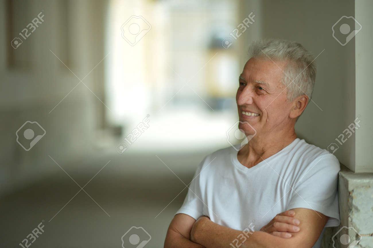 Portrait of happy senior man at home - 144529342