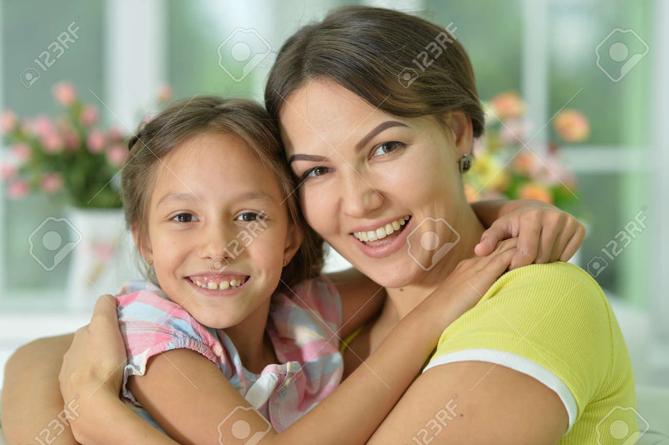 Portrait of a charming little girl hugging with mom at home - 151616251