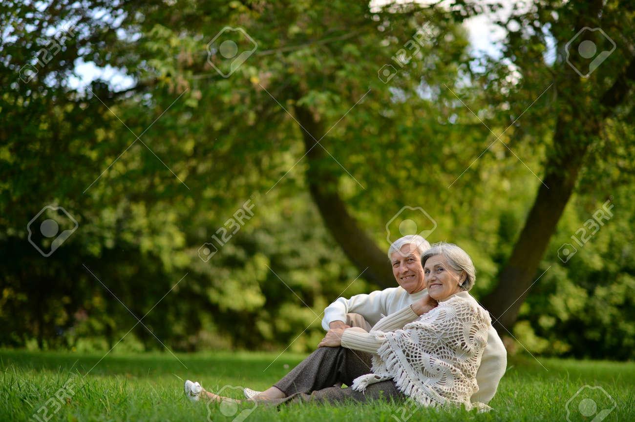 Portrait of happy senior couple sitting in park - 154941991