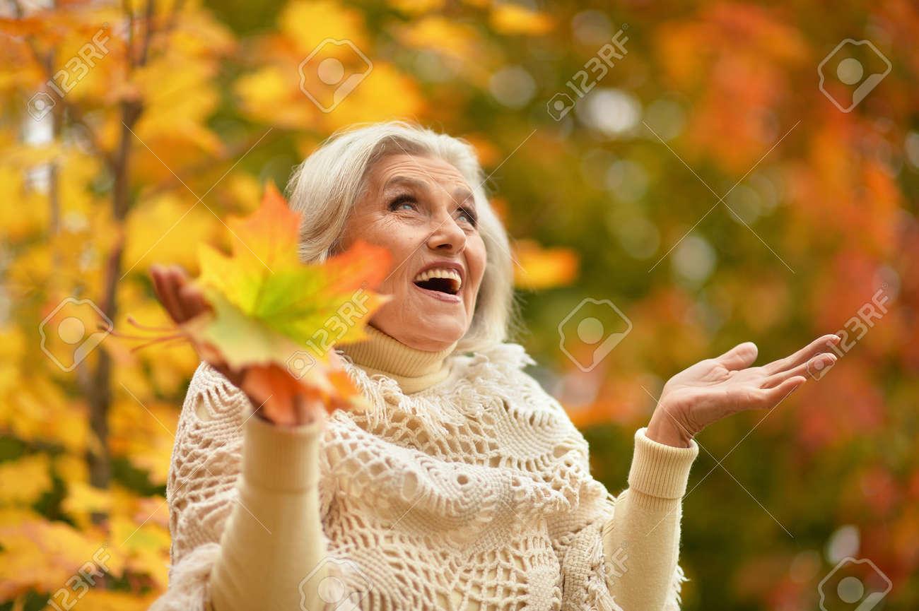 Happy senior beautiful woman in autumn park - 157849614