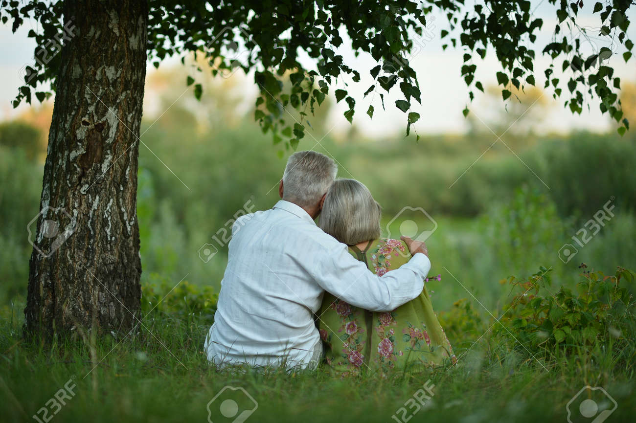 Back view of senior couple sitting on grass - 169107624