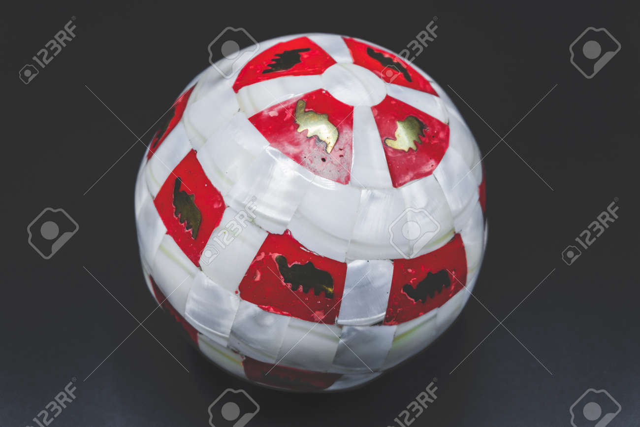 110921822 christmas wallpaper background of marbled red and white ball with golden paint isolated on black bac