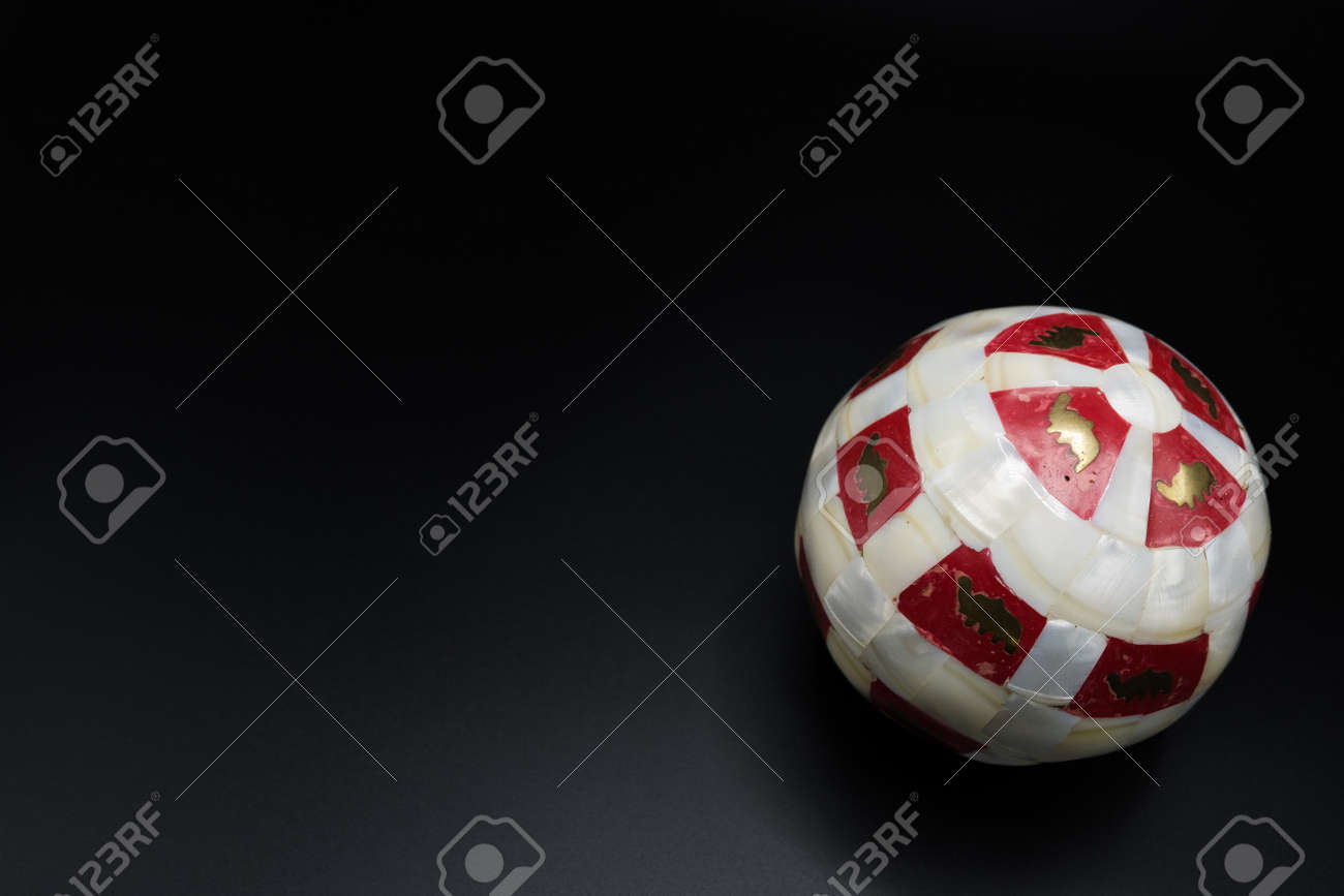 111179630 christmas wallpaper background of marbled red and white ball with golden paint isolated on black bac