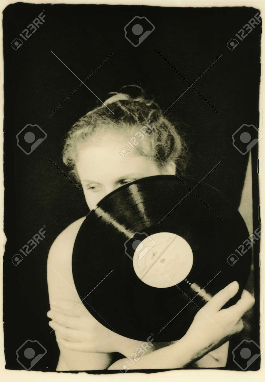 A thoughtful girl holds a musical plate in her hand  Retro style
