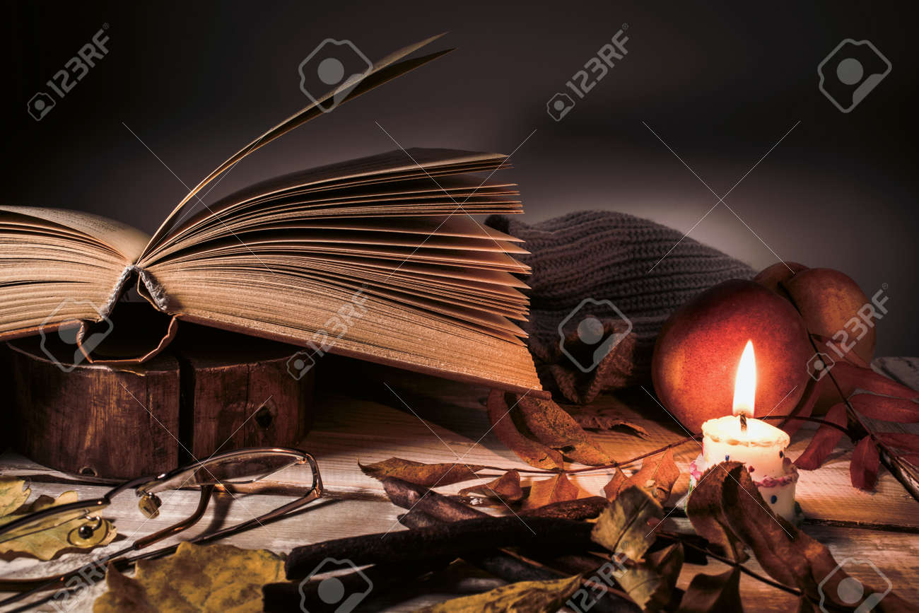 Book, glasses, fruits, a burning candle and autumn leaves on a wooden table. Autumn still life. - 131559168