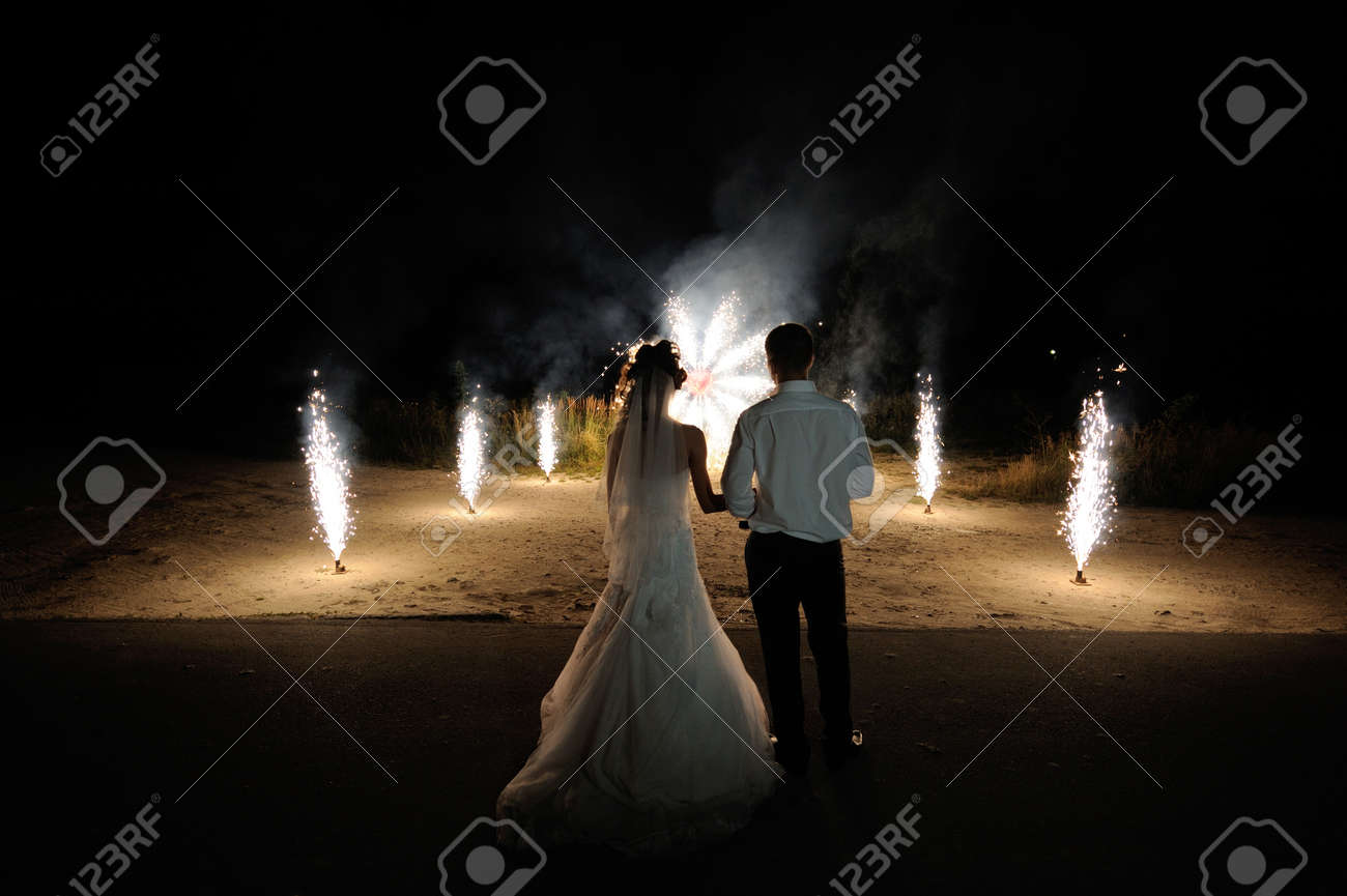 Bride and groom on the background of wedding fireworks. - 54798489