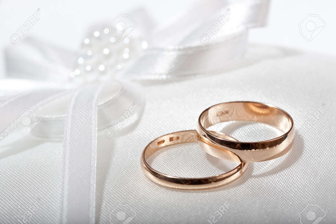 Two Wedding Rings With White Flower In The Background Stock Photo