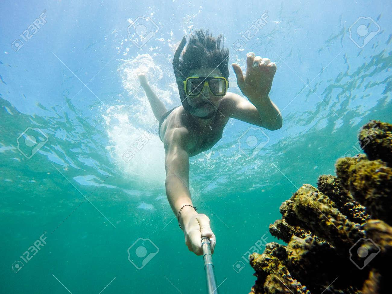 Underwater selfie shot with selfie stick. Deep blue sea. Wide angle shot. - 72142479