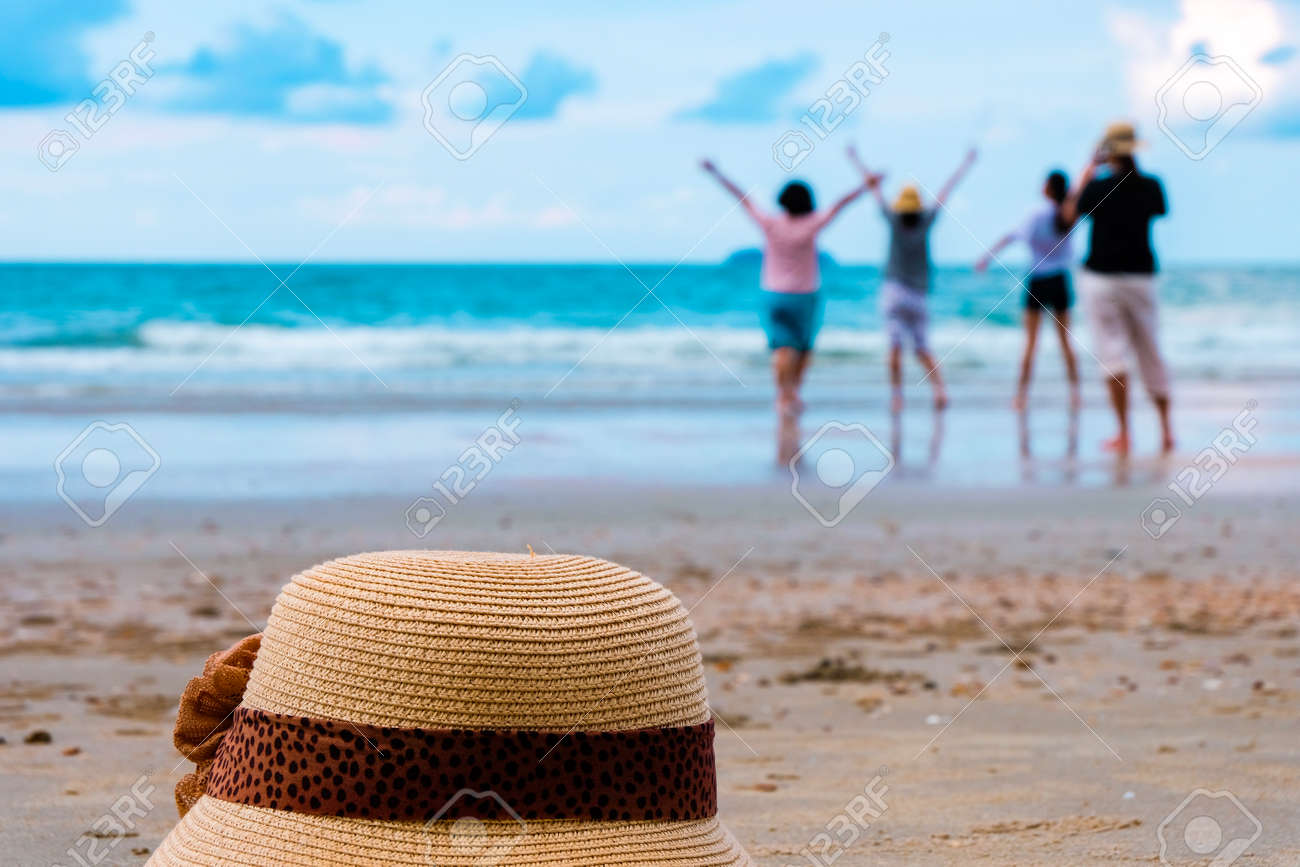 hat and group of happy young people relaxation at the beach on