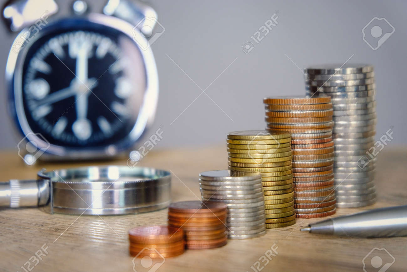 Money coins stacking with clock and magnifier glass for saving and investment concept. Employee and investor have limit time for saving and take more profit. - 103732401